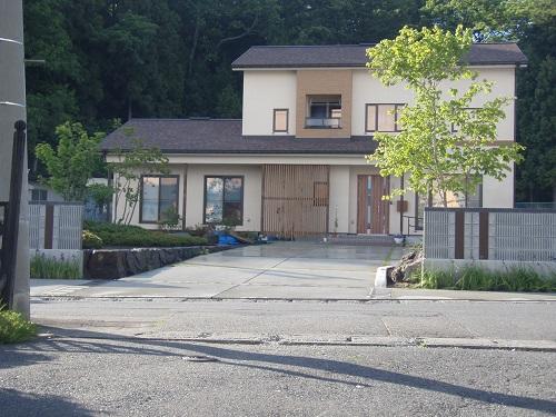 広いアプローチと曲線フェンスのある家1